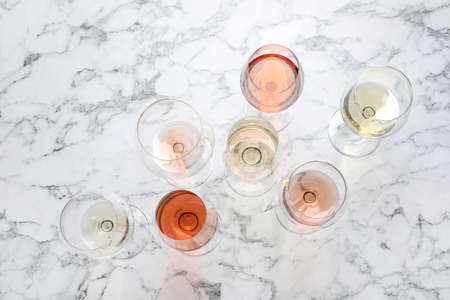 Different glasses with wine on marble background, flat lay