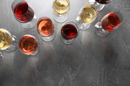 Different glasses with wine on grey background, flat lay. space for text