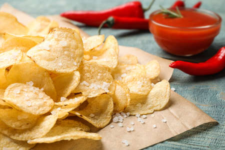 Delicious crispy potato chips with salt on table, closeup Stock Photo