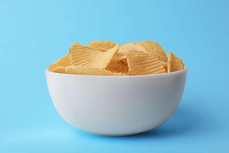 Delicious crispy potato chips in bowl on color background Stock Photo