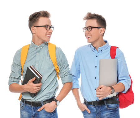Teenage twin brothers with glasses on white background