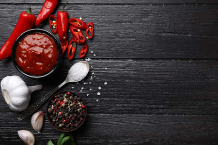 Flat lay composition with bowl of chili sauce and ingredients on wooden table. Space for text Фото со стока