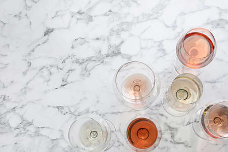Different glasses with wine on marble background, flat lay. Space for text