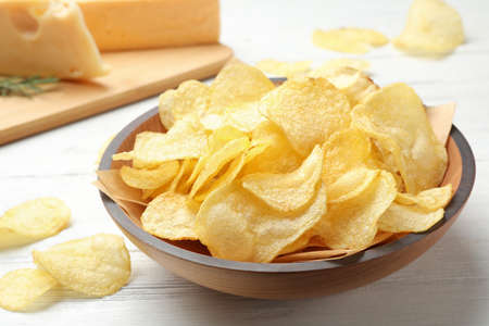 Delicious crispy potato chips in bowl on table Stock Photo