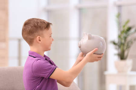 Little boy with piggy bank at home 免版税图像