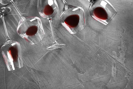 Different glasses with red wine on grey background, flat lay. Space for text
