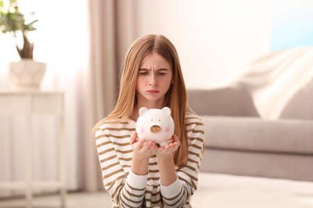 Sad teen girl with piggy bank at home