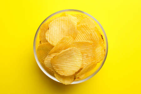 Delicious crispy potato chips in bowl on color background, top view