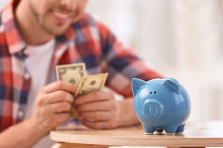 Man with piggy bank and money at home, closeup