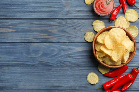 Flat lay composition with delicious crispy potato chips on wooden table, space for text