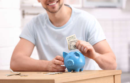 Man with piggy bank and money at home, closeup Imagens - 124724769
