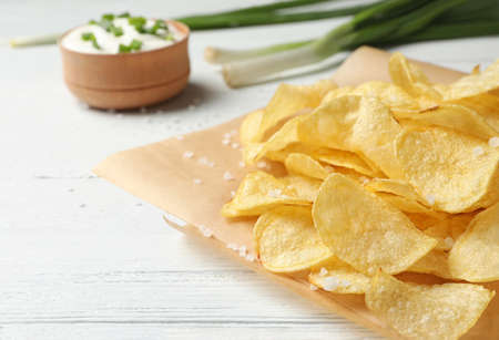 Delicious crispy potato chips on table, space for text Stock Photo