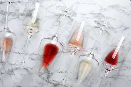 Glasses with different wine on marble background, flat lay