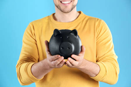 Man with piggy bank on color background, closeup Imagens - 124724970