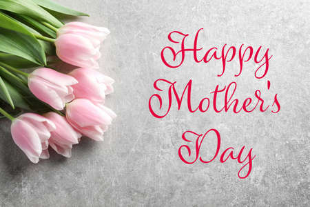 Beautiful bouquet of tulips and text Happy Mothers Day on grey background, top view