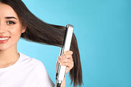 Happy woman using hair iron on color background. Space for text 스톡 콘텐츠