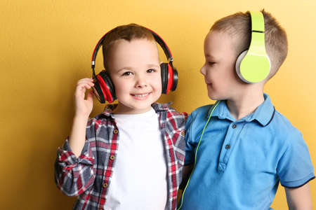 Portrait of cute twin brothers with headphones on color background