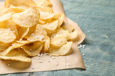 Delicious crispy potato chips on table, closeup with space for text