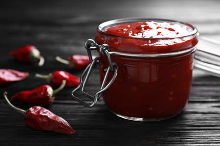 Jar of chili sauce on wooden table, closeup. Space for text Stock Photo - 124725200