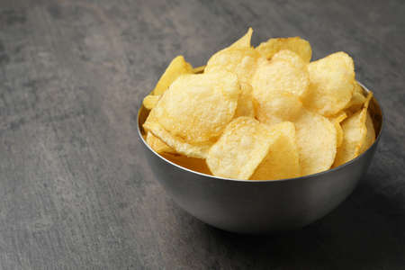 Delicious crispy potato chips in bowl on table, space for text Stock Photo