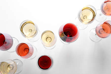 Different glasses with wine on white background, top view