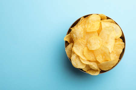 Delicious crispy potato chips in bowl on color background, top view with space for text