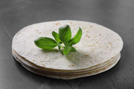 Stack of tasty tortillas with basil leaves on grey table, closeup