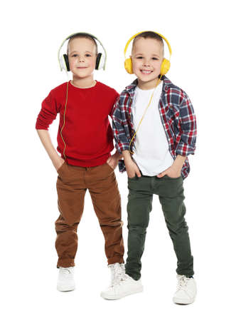 Full length portrait of cute twin brothers with headphones on white background Standard-Bild