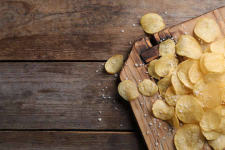 Board with delicious crispy potato chips on wooden table, top view. Space for text Stock Photo