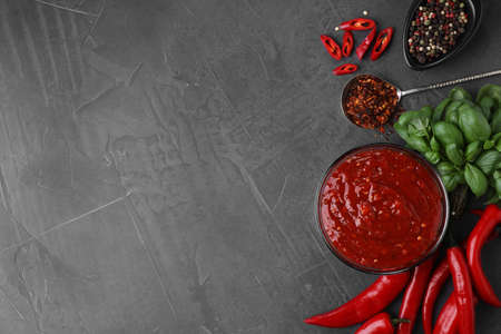 Flat lay composition with bowl of chili sauce and ingredients on grey table. Space for text