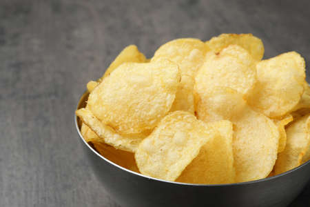 Delicious crispy potato chips in bowl on table, closeup