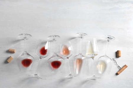 Different glasses with wine on light background, flat lay