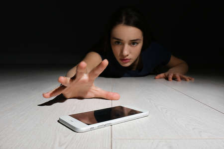 Lonely woman reaching out for smart phone on floor indoors. Internet addiction