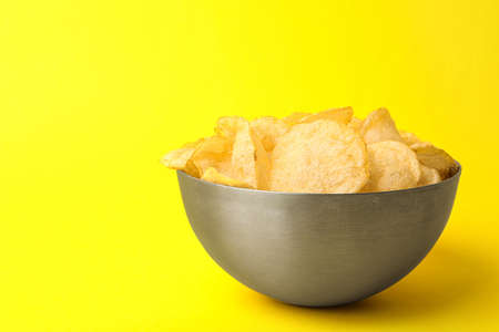 Delicious crispy potato chips in bowl on color background, space for text Stock Photo