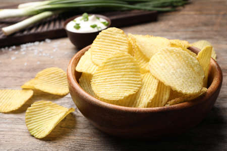 Delicious crispy potato chips in bowl on table, closeup with space for text Stock Photo