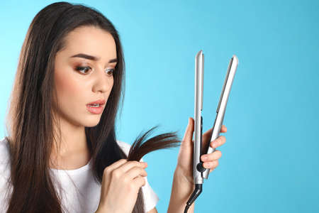 Emotional woman with hair iron on color background Standard-Bild