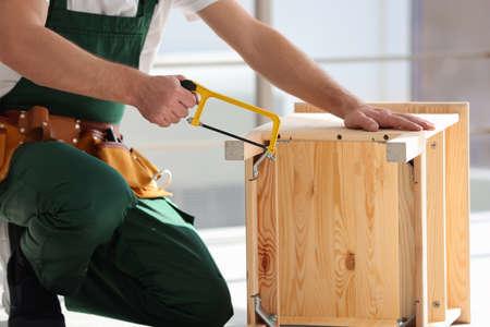 Carpenter in uniform making furniture indoors, closeup. Professional construction tools Stock Photo