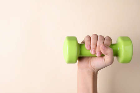 Woman holding vinyl dumbbell on color background, closeup with space for text