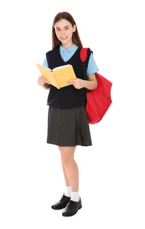 Full length portrait of teenage girl in school uniform with backpack and book on white background