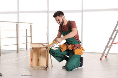 Carpenter in uniform making furniture indoors. Professional construction tools