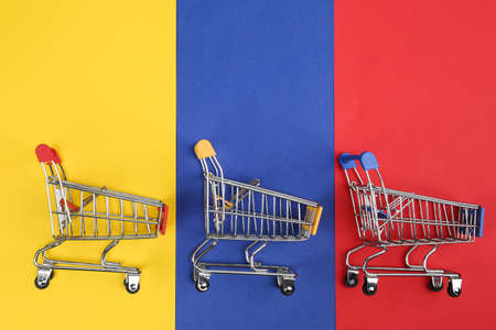 Flat lay composition with empty shopping trolleys on color background. Space for text