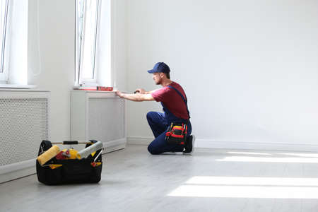 Handyman in uniform working with screwdriver indoors. Professional construction tools