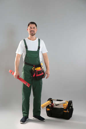 Full length portrait of professional construction worker with tools on grey background