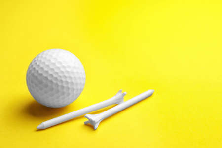 Golf ball and tees on color background, space for text. Sport equipment