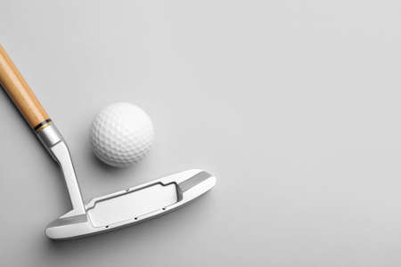 Golf ball and club on grey background, flat lay. Space for text 免版税图像
