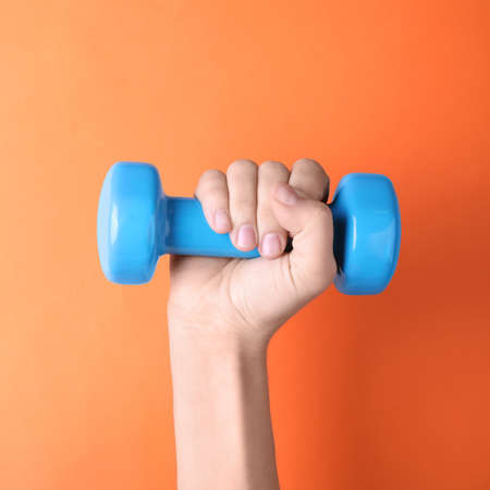 Woman holding vinyl dumbbell on color background, closeup