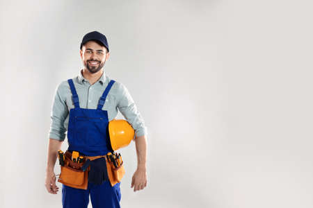 Portrait of construction worker with hard hat and tool belt on light background, space for text Stock Photo
