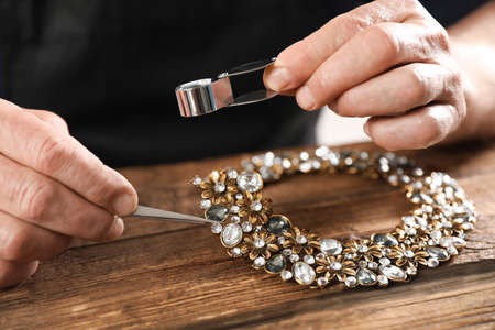 Male jeweler evaluating necklace at table in workshop, closeup Stock Photo