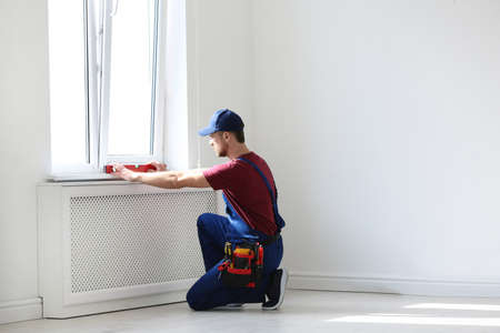Handyman in uniform working with building level indoors. Professional construction tools