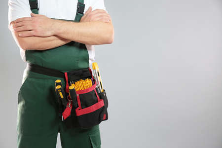 Professional construction worker with tool belt on grey background, closeup. Space for text Stock Photo